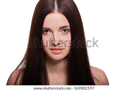 Beautiful serene young woman with a gentle expression, bare shoulders and long straight brown hair looking calmly at the camera , close up side view with turned head isolated on white - stock photo
