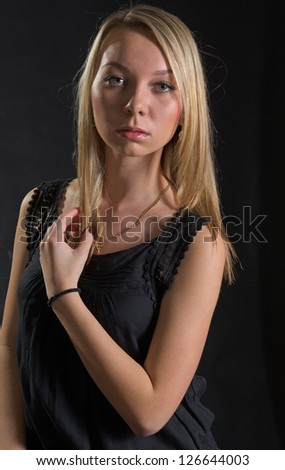 Beautiful serious young blonde lady in stylish black eveningwear posing against a dark studio background - stock photo