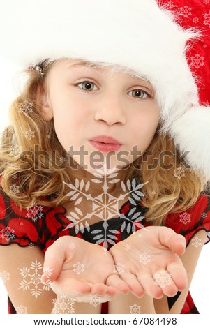 Beautiful seven year old girl in santa hat blowing snowflakes to camera. - stock photo