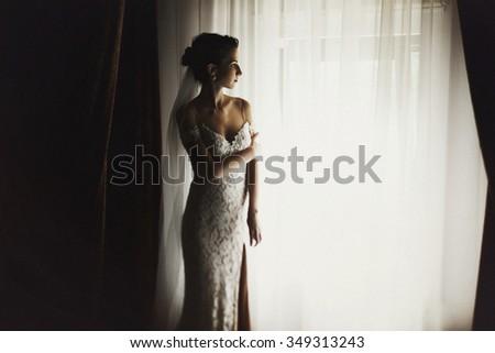 Beautiful sexual brunette bride in vintage white wedding dress near window - stock photo