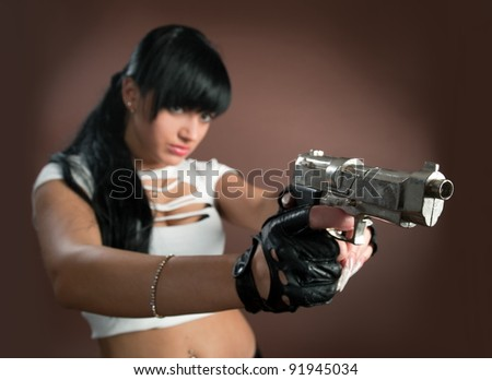 Beautiful sexual girl brunette with gun on brown background - stock photo