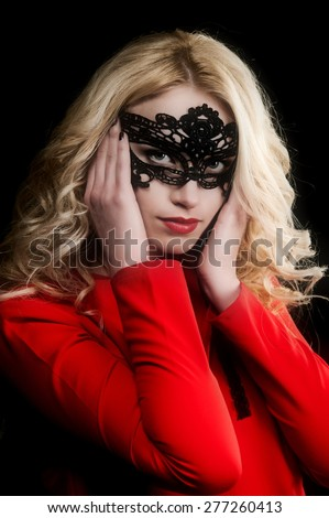 beautiful sexy blond girl in a bright red dress and a black mask posing in a studio on a black background - stock photo