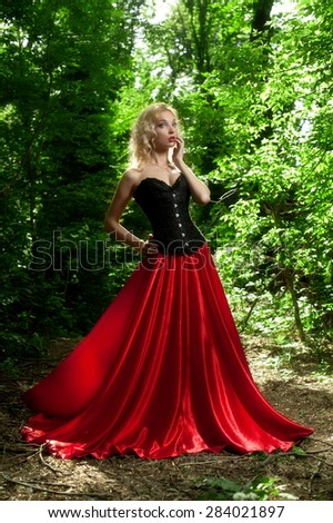 Beautiful sexy blond woman in a black corset and red skirt with a long train posing in the woods backlit - stock photo