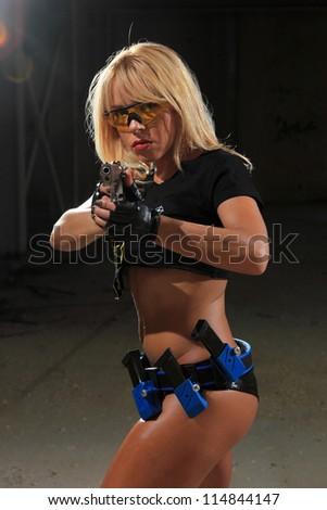 Beautiful sexy blond woman with gun - stock photo