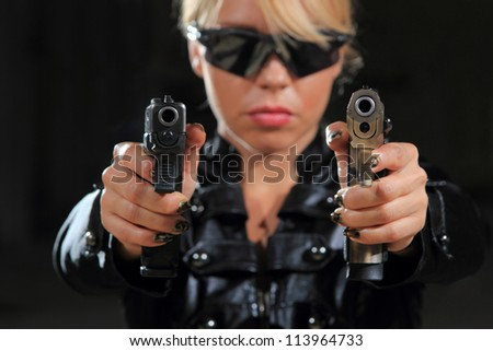 Beautiful sexy blond woman with guns - Selective focus on the gun - stock photo