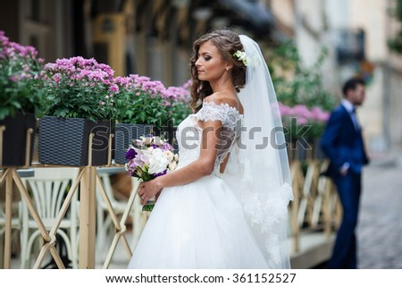 Beautiful sexy blonde bride in elegant white dress with bouquet posing near restaurant with flowers in baskets - stock photo
