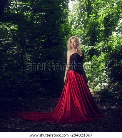 Beautiful sexy blonde girl in a black corset and red skirt with a long train poses in the forest - stock photo