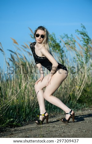 Beautiful sexy blonde girl in black body posing against a background of reeds - stock photo