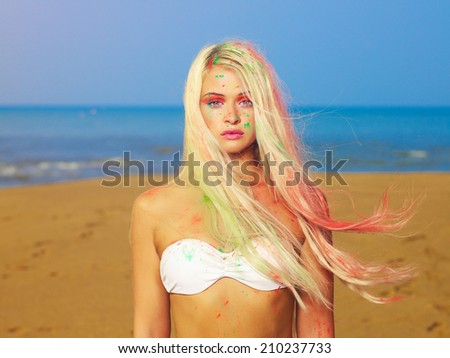 Beautiful sexy blonde in bright Indian colors at the beach - stock photo
