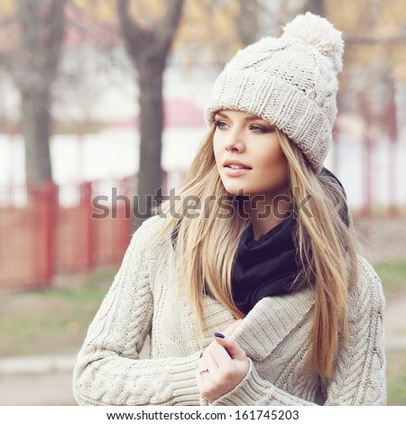 Beautiful sexy blonde standing on the autumn street in warm clothes. Wind in her hair - stock photo