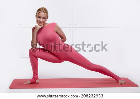 Beautiful sexy blonde with perfect athletic slim figure engaged in yoga, pilates, exercise or fitness, lead healthy lifestyle, and eats right, dressed in comfortable casual clothes relaxes meditation - stock photo