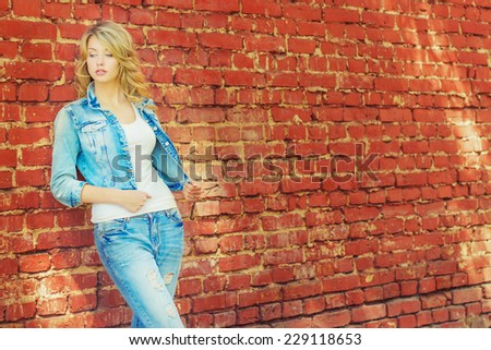 beautiful sexy blonde woman standing near a brick wall in a denim jacket and pants - stock photo
