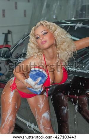 Beautiful sexy blonde woman washing a car. - stock photo