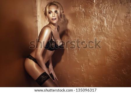 Beautiful sexy blonde woman wearing black sensual lingerie, posing. - stock photo