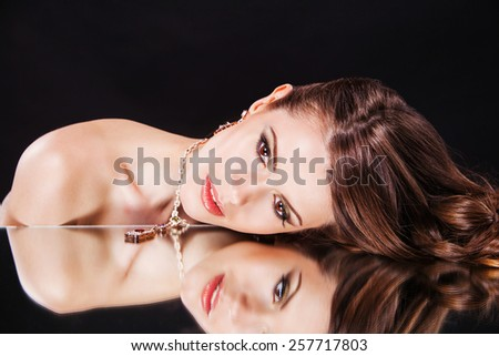 beautiful sexy brunette girl female model with bright makeup and her reflection in mirror table - stock photo
