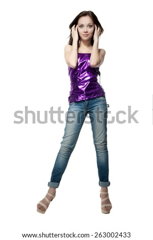 Beautiful sexy brunette girl in jeans and shiny blouse with headphones posing on a white background isolated - stock photo