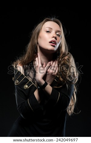 Beautiful sexy brunette girl posing on a black background in an evening dress - stock photo