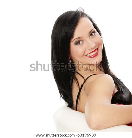 Beautiful sexy brunette in evening dress sitting, isolated on white - stock photo