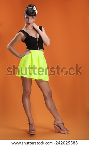 Beautiful sexy brunette pin up girl in fluorescent skirt - stock photo