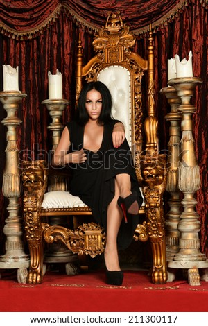 Beautiful,sexy , brunette woman sitting on throne - stock photo