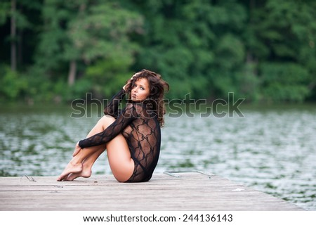 Beautiful sexy brunette woman wearing black panties and body-stocking sitting by the lake  - stock photo