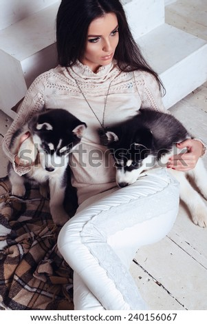 beautiful sexy brunette women with long straight hair wearing in sweater,trousers and necklace and relaxing at home,sitting on the wood floor near staircase,and holding a cute little puppies of Husky - stock photo