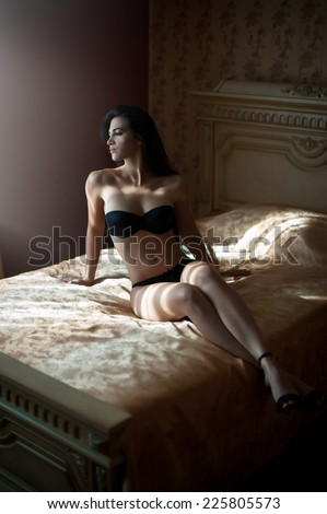 Beautiful sexy brunette young woman wearing black lingerie lying in bed. Fashionable female with attractive body posing provocatively, indoor shot. Sensual girl with high heels shoes on bed in hotel - stock photo