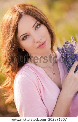 Beautiful sexy caucasian woman sitting on the grass on summer meadow. Portrait of the young beautiful smiling woman outdoors. - stock photo