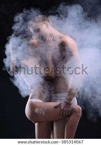 Beautiful sexy couple in love. Both of them in underwear. Photo in the dark with smoke on the background. - stock photo