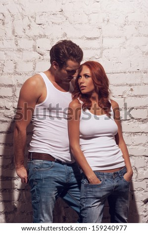 Beautiful sexy couple looking at each other. Wearing white T-shirts and jeans  - stock photo