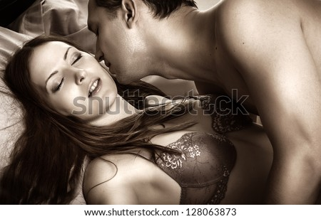 Beautiful sexy couple of  lovers. Young man kissing woman in darkness bedroom on bed - stock photo