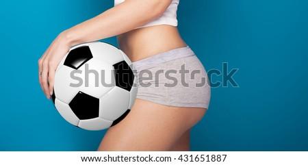 Beautiful sexy fan of football championship. Fit girl holding ball. Blue background. - stock photo