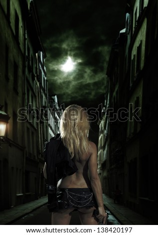 beautiful sexy girl holding gun in the streets - stock photo