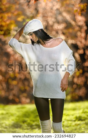 Beautiful sexy girl in white posing in park in autumn day. Beautiful elegant woman with white cap in autumnal park. Young pretty brunette woman with leggings and long legs in the forest - stock photo