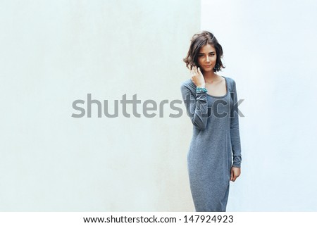 beautiful sexy girl smiling in the background of a wall - stock photo
