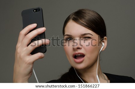 Beautiful sexy girl with a phone and headphones - stock photo