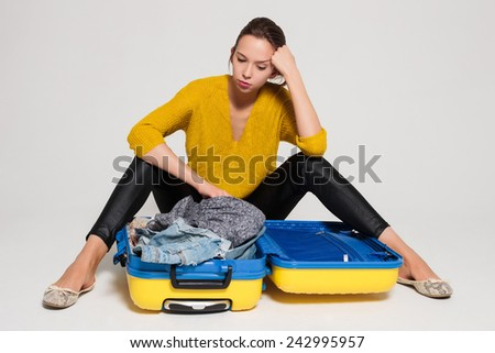 Beautiful sexy girl with a yellow suitcase loves to travel - stock photo