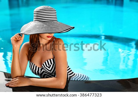 Beautiful Sexy Girl With Healthy Skin In Elegant Striped Bikini, Sun Hat Relaxing In Swimming Pool Water In Resort Spa Hotel On Travel Holidays Vacation. - stock photo