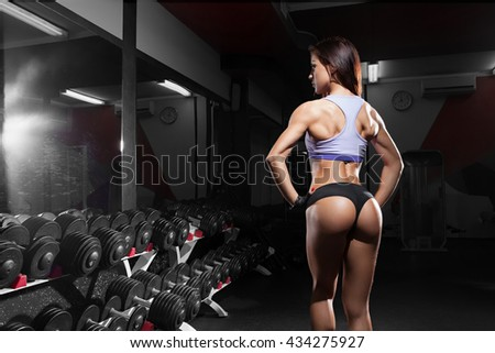 Beautiful sexy girl with perfect abdominal muscles at the gym. The concept of a healthy lifestyle and exercise. Strong woman. Feminism. - stock photo