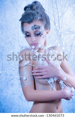 Beautiful sexy, glamorous girl with drawings on the body in an image of the queen of winter. Blue toning - stock photo