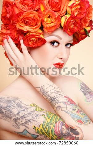 Beautiful sexy glamorous girl with tattoos and fancy wig of bright orange roses - stock photo