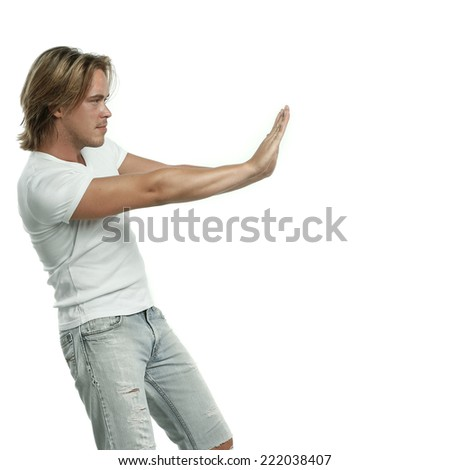 beautiful sexy man casual dressed in jeans and white shirt or t-shirt is pointing with his hands  - stock photo