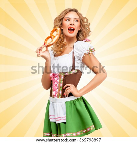 Beautiful sexy Oktoberfest woman wearing a traditional Bavarian dress dirndl with open mouth eating a pretzel on colorful abstract cartoon style background. - stock photo