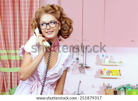 Beautiful sexy pin-up girl talking on the phone on a pink kitchen. Fashion. - stock photo