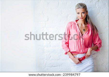Beautiful sexy sensual blonde girl in the pink jacket in the Studio against the wall - stock photo