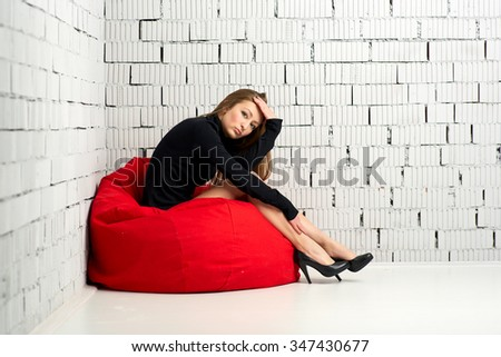 Beautiful sexy sensual brunette girl in the  Studio against the white brick wall - stock photo