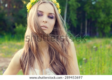 beautiful sexy sweet girl with long hair and a wreath of yellow roses on his head in the field, the wind blowing her hair - stock photo