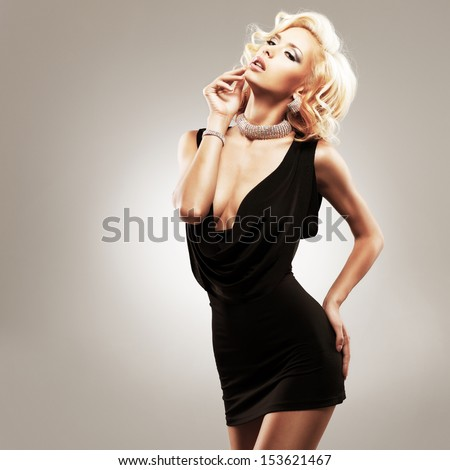Beautiful sexy white woman in black dress posing at studio - stock photo