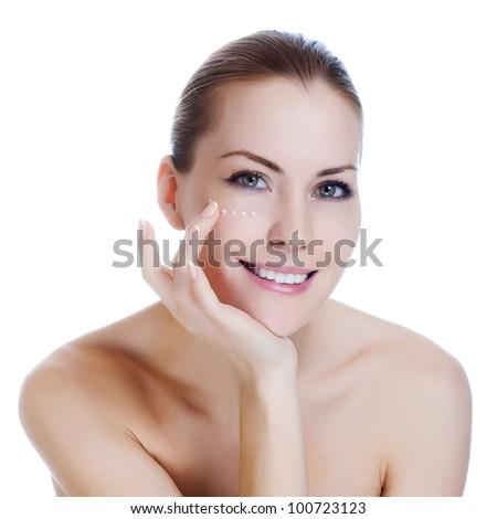 Beautiful sexy woman applying cosmetic cream on skin near eyes - stock photo