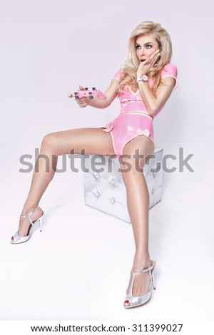 Beautiful sexy woman hair curl and blonde long hair and sensually looking on white background sit of silver cristal cube and hand-held gaming console pad and game she looks like a doll in a pink dress - stock photo